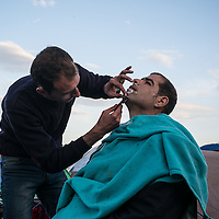 A refugge been shaved by another migrant is een in the makeshift camp at the Greek Macedonian border not far frim the Greek village of Idomeni, Greece. FEDERICO SCOPPA/CAPTA