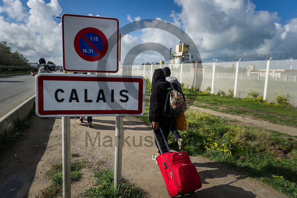Calais, Frankreich - 17.10.2016<br /> Migranten laufen aus dem Weg aus dem Dschungel von Calais an dem Ortsschild von Calais vorbei. Das Fluechtlingscamp an der Kueste zum Aermelkanal soll laut franz&ouml;sischer Regierung in den n&auml;chsten Tagen geraeumt werden. In dem Camp leben um die 1000 Fluechtlinge und warten auf die Moeglichkeit zur Weiterreise durch den Eurotunnel nach Gro&szlig;britannien. Photo: Foto: Markus Heine / heineimaging<br /> <br /> Calais, France - 2016/10/17<br /> Migrants pass on their way out of the Calais Jungle the town sign of Calais. The refugee camp on the coast to the English Channel is to be cleared in the next few days, according to the French government. In the camp live around the 1000 refugees and wait for the possibility to travel further through the Eurotunnel to the UK. Photo: Foto: Markus Heine / heineimaging<br /> <br /> ------------------------------<br /> <br /> Ver&ouml;ffentlichung nur mit Fotografennennung, sowie gegen Honorar und Belegexemplar.<br /> <br /> Bankverbindung:<br /> IBAN: DE65660908000004437497<br /> BIC CODE: GENODE61BBB<br /> Badische Beamten Bank Karlsruhe<br /> <br /> USt-IdNr: DE291853306<br /> <br /> Please note:<br /> All rights reserved! Don't publish without copyright!<br /> <br /> Stand: 10.2016<br /> <br /> ------------------------------