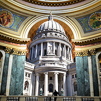 Wisconsin State Capitol Building Composite in Madison, Wisconsin<br /> Two photos of Madison, Wisconsin, are: 1) The gold-leaf covered &ldquo;Wisconsin&rdquo; statue. This symbolizes &ldquo;Forward&rdquo; on top of the world&rsquo;s largest white granite dome of Wisconsin&rsquo;s State Capitol completed in 1917. 2) The interior rotunda. This was constructed with 43 types of stone from across Europe and the Midwest. The inside is also graced with lavish arches, stencils and murals. Shown are two of four mosaics. Each one is made from 100,000 pieces of glass. On the left is &ldquo;Government&rdquo; and on the right is &ldquo;Liberty.&rdquo;
