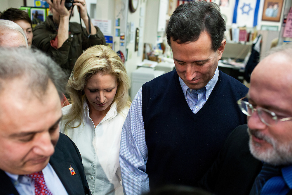 Republican presidential candidate Rick Santorum, third from left, prays before meeting with voters at Hollis Pharmacy and General Store on Saturday, January 7, 2012 in Hollis, NH. Brendan Hoffman for the New York Times