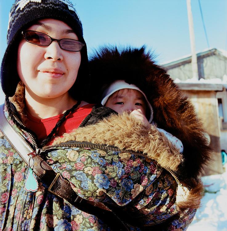 Brenda Kara Tokeinna and her daughter, Edna, outside of their home in Shishmaref, Alaska in March 2010.