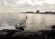 A surfer catches a small wave at the 91st Street surf break, Rockaway Beach, Queens, NY.
