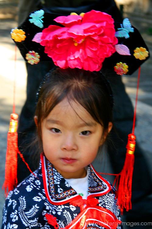 Asia; Asian; China; Chinese; PRC; People's Republic of China; Beijing; girl; child; kid; dress; costume; hat; ethnic; minority; tassles; face; young; clothes; traditional; heritage; person;