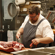 SHOT 8/14/13 6:58:15 PM - Justin Brunson, Owner and Executive Chef at Old Major restaurant in Denver, Co. Includes images of menu items : The Nose to Tail Plate : confit rib, pork chop, crispy belly, city ham, crispy ear, Denver Bacon Co. barbecue beans, cole slaw and corn bread $29 and Pan Seared Scallops : baby vegetables, fregola, spinach purée, toasted pine nuts, roasted garlic vinaigrette $27. The restaurant focuses on heritage-raised meats from Colorado farms, features an in-house butchery program and bills itself as contemporary farmhouse cuisine. (Photo by Marc Piscotty / © 2013)