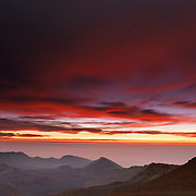 An approaching storm results in a fiery sunrise over the Haleakala crater in Haleakala National Park, Maui, Hawaii. The approaching clouds are blurred by a 30-second exposure.