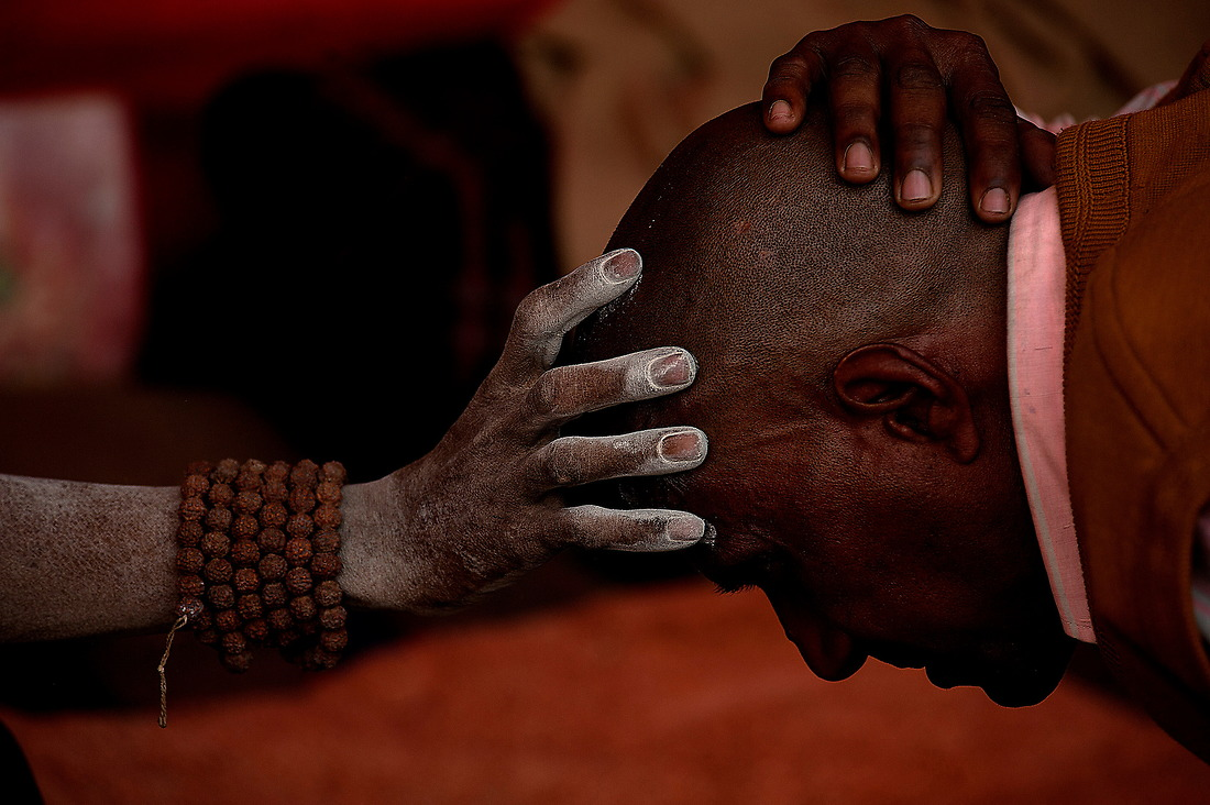 A Sadhu ((holy man) reaches out and blesses a man on February 6, 2013 in Allahabad, India during the Kumbh Mela. Other activities besides bathing include religious discussions, devotional singing, mass feeding of holy men and women and the poor, and religious assemblies. — © Jeremy Lock/
