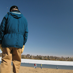A man stands looking over the beach where a small group of people have gathered in the distance