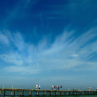 ANNA MARIA ISLAND, FL -- February 2, 2005 -- As clouds feather across a blue sky, visitors walk the wood planks of the historic Anna Maria City Pier, built in 1910, on Anna Maria Island Wednesday morning.