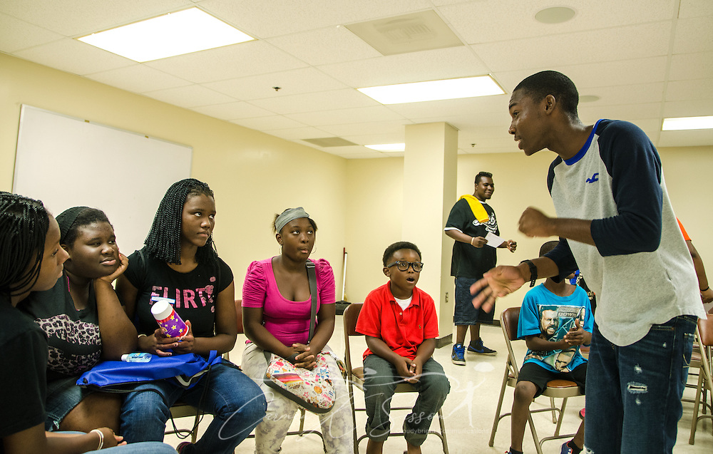 Larry Johnson, 18, talks to students in the Young People's Project about how the program has changed his life, Aug. 3, 2013, in Jackson, Miss. From left are: Trinity Stewart, 14; Raven Horton, 15; Aalyah Stewart, 15; Nyah Sansom, 13; and Handsome Jordan, 8. YPP focuses on math literacy as a way to empower youth and help them overcome obstacles to their success. (Photo by Carmen K. Sisson/Cloudybright)