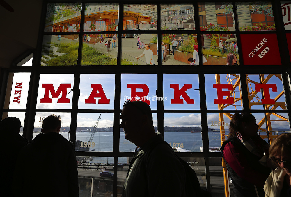 Sunlight streams into Pike Place Market as Seattleites get a break from gloomy skies and rain. (Ken Lambert / The Seattle Times)