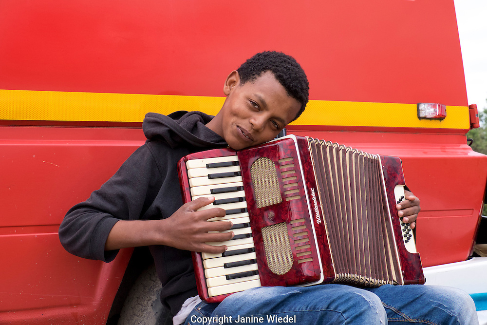 Young boy playing music in The Calais Jungle Refugee and Migrant Camp in France