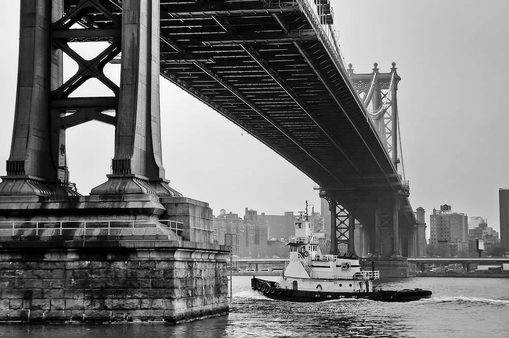A tugboat passes down the Manhattan Bridge as seen from DUMBO, Brooklyn, New York
