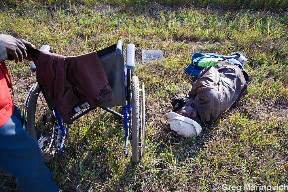 A man in an advanced stages of Aids has fallen out of his wheelchair while being poushed by a friend after a visit to a clinic for Aids and HIV being sponsored by the Xstrata mining company in Breyten, Mpumalanga province, South Africa, Photo Greg Marinovich.
