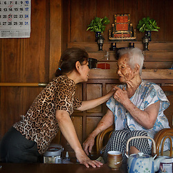 Hiromi Yohena aids her grandmother, Hana Shinjo, 103 years old, at her home. Even as a centenarian, Shinjo is able to live by herself and is cared for by neighbors and family.