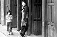 A young girl and her mum wait in front of their house.