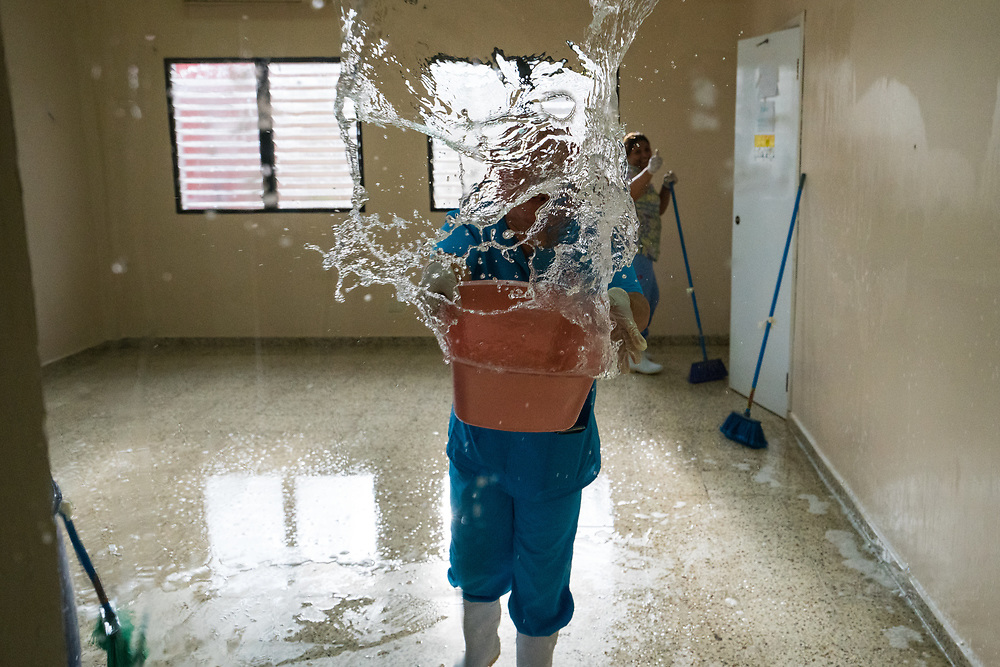 Hospital staff throw water on a window in the waiting room to clean during a slow period at Occidente Hospital in Santa Rosa de Copan, Copan, Honduras Feb. 28, 2017. Photo Ken Cedeno
