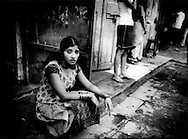"""(Intro) Selling Spring, or """"Baishun"""" in Japanese, reflects age-old attitudes towards prostitution, this form of servitude.  The portraits examine the humanity of young women, many of whom would not even provide a first name, inlisted in selling their spring. ..(Caption) Unaffected by the economic upturn in Mumbai, India.  Worn out sex worker gazes out from her stoop on Falklands Road, the heart of the red light district, Mumbai, India.  Some sources put the level of HIV infection at 60% among Mumbai's sex workers because of low condom use."""