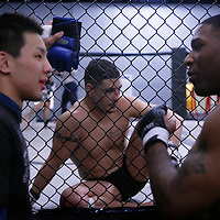 Jackson's/Winklejohn's: January 23, 2012 UFC fighter Diego Sanchez rests inside the cage as Willie Parks and Riki Nobuta talk during coach  Greg Jackson's class at Jackson's/Winkeljohn's in Albuquerque, NM