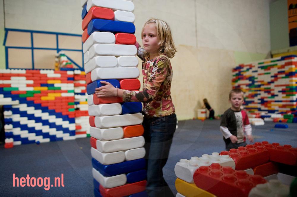 kinderen, jongens en meisjes spelen in een binnespeeltuin met bouwblokken