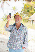 mature man taking a selfie on the beach in Florida