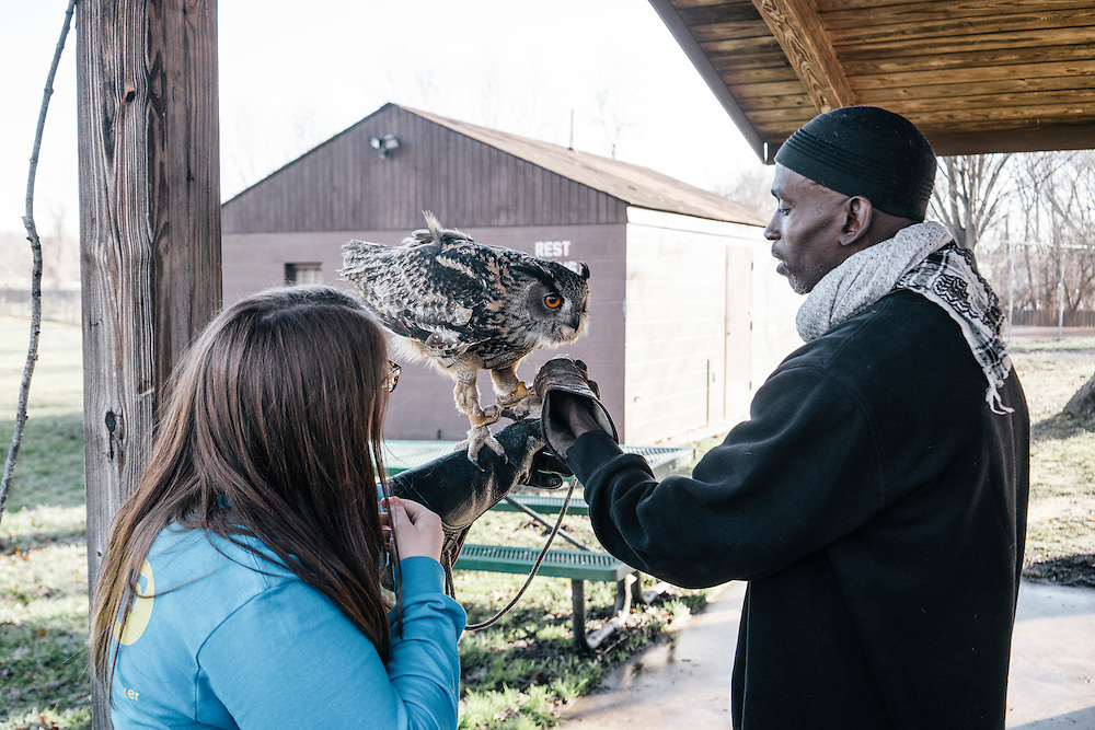 Claire Adamski, left, 21, from University of Minnesota Morris, holds Hoots, the Eurasian eagle owl before the annual Lower Beaverdam Creek cleanup on March 17, 2016.
