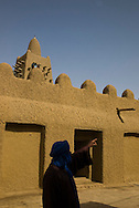 A man dressing Tuareg  clothes pointing near Djingareyber Mosque in Timkuktu, Mali.