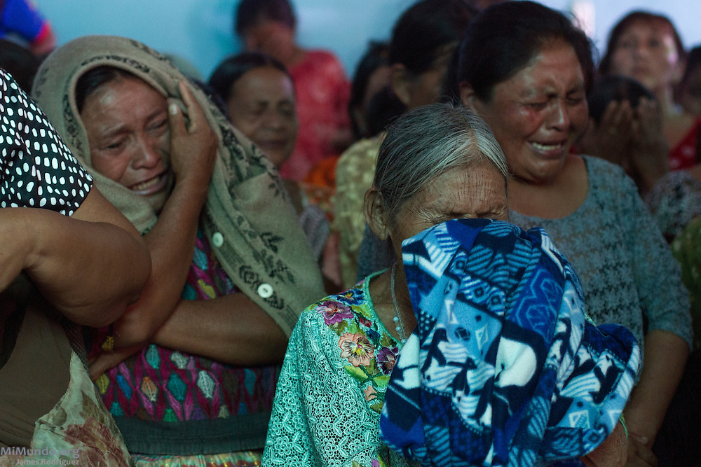 Matilde Dometila Ja Chiquin (forefront) covers her face as she cries during a prayer before receiving the skeletal remains of her son Santiago Jalai Ja. The positively identified male remains of six wartime victims, including Santiago's, are returned to their appropriate families by members of the Guatemalan Forensic Anthropology Foundation (FAFG) in the Poqomchi' Mayan hamlet of Pambach, 38 kilometers from Cobán. The remains, matched through DNA samples, were exhumed from grave 17 of the Regional Command of Training and Peacekeeping Operations (CREOMPAZ), formerly known as Military Zone 21 in Cobán. All six men were taken by the army during an incursion to the village on June 2, 1982, during the de facto government of Efraín Ríos Montt, and were never seen again. A total of 64 skeletal remains were recovered from grave 17, the majority of which bore evidence of violence such as blindfolds and bound hands and feet. Pambach, San Cristobal Verapaz, Alta Verapaz, Guatemala. November 22, 2013.