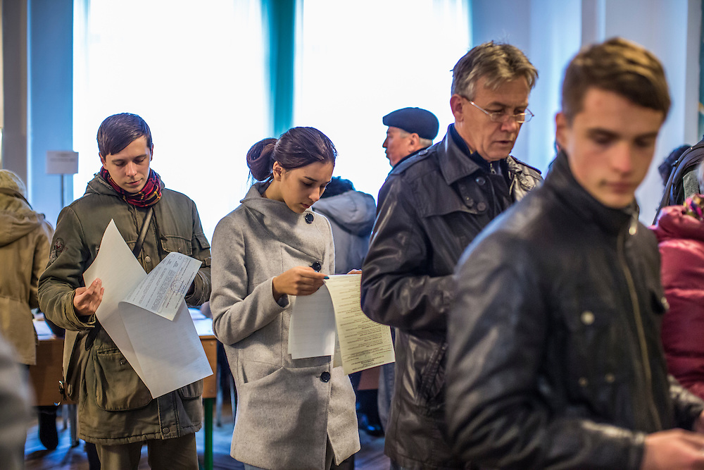 KIEV, UKRAINE - OCTOBER 26: Voters wait their turn to fill out their ballots for parliamentary elections on October 26, 2014 in Kiev, Ukraine. Although a low turnout is expected in the east of the country amid continued fighting between Ukrainian forces and pro-Russian separatists, Ukraine is expected to elect a pro-Western parliament in a further move away from Russian influence. (Photo by Brendan Hoffman/Getty Images) *** Local Caption ***
