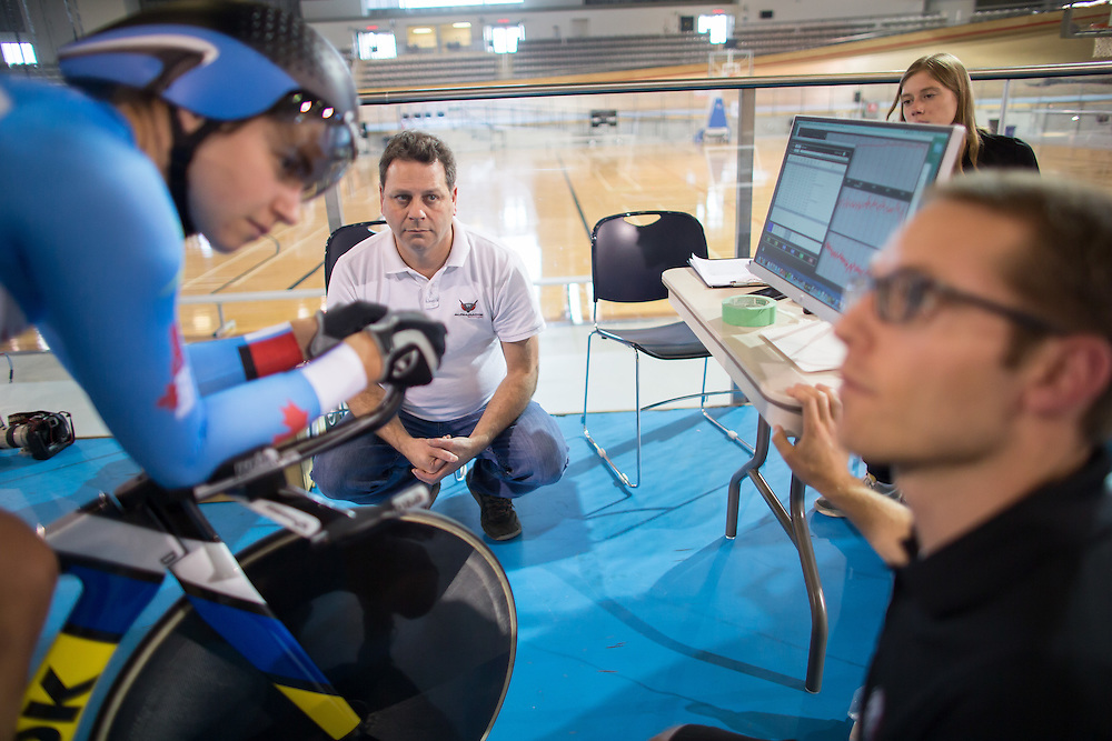 Milton, Ontario ---2015-09-30--- National team pursuit  member Annie Forman-Mackie gets into position on her bike as Cycling Canada aerodynamicist Andy Froncioni (C)  sport physiologist Mike Patton (R) and performance scientist Emily Wood discuss possible changes during aerodynamic testing at the Mattamy National Cycling Centre velodrome in Milton, Ontario, September 30, 2015. <br /> GEOFF ROBINS The Globe and MailMilton, Ontario