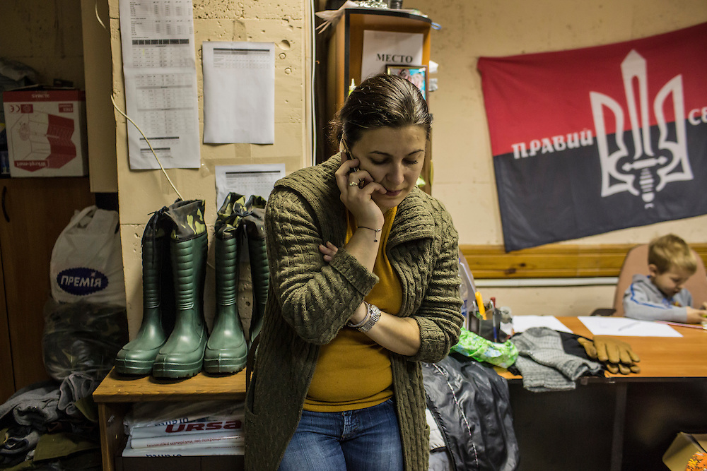 DNIPROPETROVSK, UKRAINE - NOVEMBER 16, 2014:  Natalia Naumenko, 38, the owner of a travel agency, talks on the phone at the Dnipropetrovsk Volunteer Logistics Center, a charity organization that produces supplies for pro-Ukrainian fighters battling rebels in the country's East, in Dnipropetrovsk, Ukraine. CREDIT: Brendan Hoffman for The New York Times