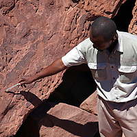 Africa, Namibia, Twyfelfontein. Guide at petroglyphs of twyfelfontein, a UNESCO World Heritage Site.