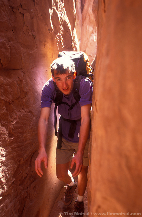 Dan Aylward squeezes through a slot in the Fiery Furnace in Arches National Park, Utah.
