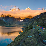 Sunrise illuminates the Cordillera Huayhuash above Carhuacocha lake campground (13,600 feet) in the Andes Mountains, Peru, South America. Peaks from left to right are: Siula Grande, Yerupaja Grande (6635 m or 21,770 ft, highest point in the Amazon watershed), Yerupaja Chico, and Mount Jirishanca (Icy Beak of the Hummingbird). Day 3 of 9 days trekking around the Cordillera Huayhuash. This panorama was stitched from 6 overlapping photos.