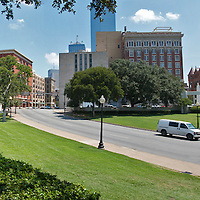"Panoramic view of the Texas Schoolbook Depository (on left) and the road where JFK was assassinated in Dallas, Texas. Image was taken from the grassy knoll and shows the two ""x's"" on the road where the bullets hit the President."
