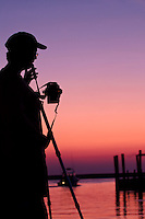 A photographer sets up to take a picture of Wancheese harbor as the sun lights the sky.