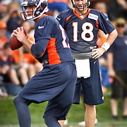 SHOT 7/25/13 9:30:44 AM - Denver Broncos quarterback Peyton Manning #18 watches fellow quarterback Brock Osweiler #17 as they run through drills during opening day of the team's training camp July 25, 2013 at Dove Valley in Englewood, Co.  (Photo by Marc Piscotty / © 2013)