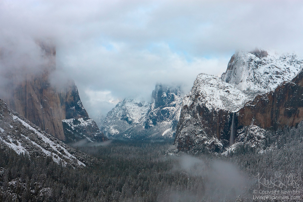 A winter storm blankets the Yosemite Valley with fresh snow. Yosemite National Park receives the most snow in January and February with an average snow depth of 6.5 inches (16.5 centimeters) on the valley floor during those months. Bridalveil Fall, one of Yosemite's iconic waterfalls, is visible in the right of the image. El Capitan, the largest exposed granite face in the world, is shrouded in snow clouds at the left. Half Dome is visible at the center-right.
