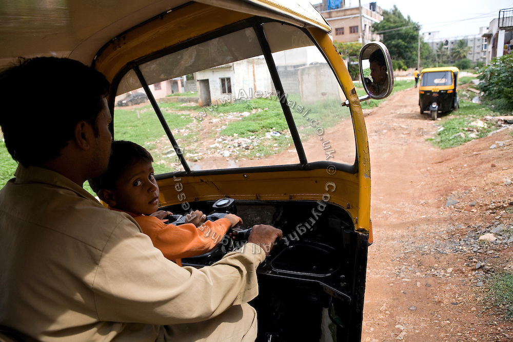 Shafiq Syed, 34, is driving his rickshaw with his younger son, Nadeem, 4, along the streets surrounding the poor neighbourhood in Bangalore, Karnataka, India, where he now lives with his family. Shaifq has been the main character of the Cannes' Camera D'Or 1988 winner Salaam Bombay, but after the movie he failed to become a star, fell back into poverty and lived on the streets for years before he became a rickshaw (tuk-tuk) driver in his home city of Bangalore, Karnataka State, India.