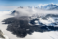 A 4,000-foot-high mountainside released approximately 120 million metric tons of rock in 60 seconds during a landslide onto the Lamplugh Glacier in Glacier Bay National Park and Preserve. In an interview with the Anchorage Dispatch News, geophysicist Colin Stark of Columbia University's Lamont-Doherty Earth Observatory, described the slide as &ldquo;exceptionally large.&rdquo; He compared the massive landslide to roughly 60 million medium SUVs tumbling down a mountainside.<br /> <br /> The slide occurred on the morning of June 28  in a remote area of Glacier Bay National Park in southeast Alaska. It was first observed by Paul Swanstrom, pilot and owner of Haines-based Mountain Flying Service. Swanstrom noticed a huge cloud of dust over the Lamplugh Glacier during a flightseeing tour of Glacier Bay National Park several hours after the slide occurred. Swanstrom estimates the debris field to be 6.5 miles long, and one to two miles in width.<br /> <br /> Even two days later, as this aerial photo of the Lamplugh Glacier landslide shows, a dust cloud remained over the unstable mountainside due to still tumbling rock.