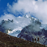 Trekkers walk towards a 14,200 foot pass beneath Nevado Terihuay (17,500 feet elevation), in the Cordillera Urubamba between Lares and Patacancha, near Ollantaytambo, Peru, South America. The moderately strenuous trek from Lares to Patacancha traverses rugged, little-visited country in the Cordillera Urubamba across passes at 13,800 and 14,200 feet elevation. A five hour bus ride from Cuzco reaches Lares, where you can soak in developed hot spring pools. Llamas and horses carried our loads for two nights of camping at 12,500 feet elevation.