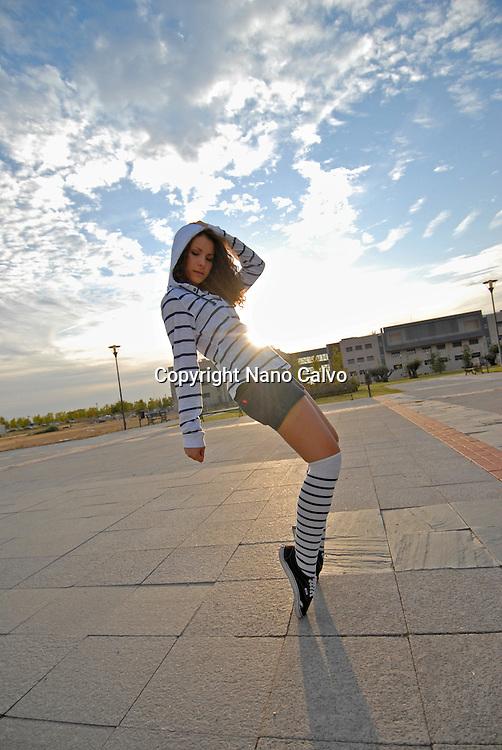 Cute teen dancer performing street dance balance movements