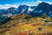 Couple with backpacks hiking on Sahale Arm Trail, Cascade Pass, North Cascades National Park, Washington.