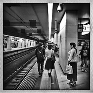Couple passes security cameras on the platform for the Shinjuku-bound trains, as one security camera seems to hand commuters onto the next security camera.  Tokyo, Japan.