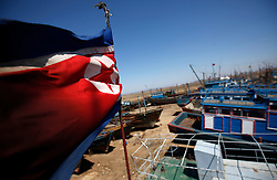 A North Korean flag flies over boats in a Chinese shipyard along the Yalu River bordering North Korea near the town of Sinuiju in Hailong village of Dandong, Liaoning Province, China on 07 April 2013. Many of the vessels operate along the Yalu River between the North Korean and Chinese border and it is not uncommon for them to fly both Chinese and North Korean flags. China on 07 April said its embassy in Pyongyang was still 'operating normally' following North Korea's warning to diplomats that it could only guarantee their safety until Wednesday. Beijing had asked North Korea to protect the safety and interests of Chinese citizens and businesses in the country.