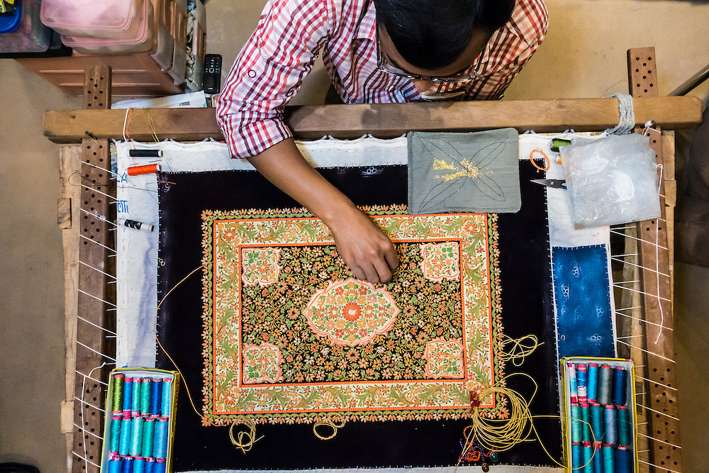 A man creating an embroidered Zardozi wall hanging viewed from above, Agra India.