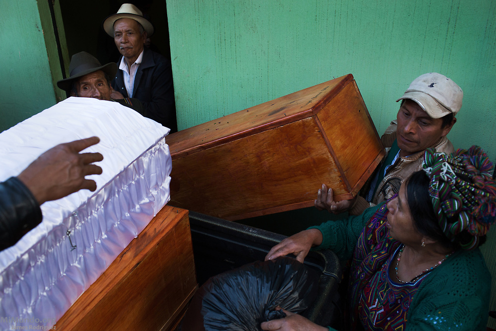 Ixil Mayan residents of Nebaj load the coffins of 36 war victims as these are returned to their surviving family members for a proper burial. Most of the victims, exhumed from mass graves in Xe'xuxcap, near Acul, starved in the mountainside while fleeing State-led repression in 1982. Most of the remains, exhumed by members of the Forensic Anthropology Foundation of Guatemala (FAFG) in 2013, were identified using DNA analysis and buried 35 years after their death. Nebaj, Quiché, Guatemala. February 2, 2017.