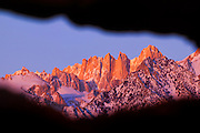 A natural window in a boulder pile in the Alabama Hills near Lone Pine, California, frames Mount Whitney at sunrise. Mount Whitney, part of the Sierra Nevada range, is the tallest mountain in the 48 contiguous United States with an elevation of 14505 feet (4421 meters).
