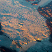 The toe of a large glacier ends at a frozen lake in this aerial view of western Greenland.