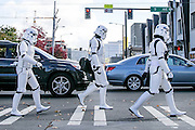 "Dino Ignacio, left, of West Seattle; Guy Evans, of Tacoma; and Casey Buxton, of Vashon Island, cross the street on their way to the EMP Museum in Seattle on Sunday. The friends are members of the 501st Legion, an all-volunteer organization that promotes interest in ""Star Wars"" while appearing at local community and charity events. They thought it would be fun to check out the EMP Museum's sci-fi exhibit while wearing their storm-trooper outfits. (Johnny Andrews/The Seattle Times)"