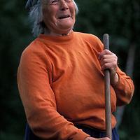 Norway, Hornindal, (MR) Lina Gausemel rakes cut grass in fields around farm in west Norway.